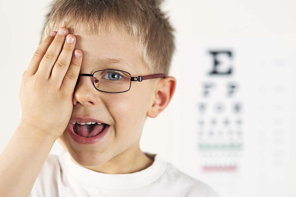 Eye examination of a smiling little boy wearing glasses. The boy is looking at the eye test chart and is saying what he sees. The boy is covering one eye.
