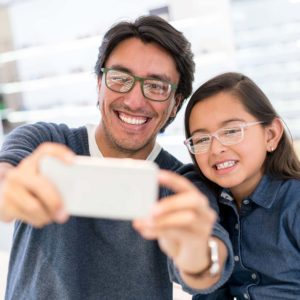 Happy father and daughter buying new glasses at the optician and taking a selfie with her cell phone